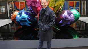 """Artist Jeff Koons poses with his sculpture """"Tulips"""" in front of Christie's at Rockefeller Plaza in New York City in 2012"""