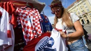 Une supportrice croate regardent les différents maillots de l'équipe nationale, le 14 juillet 2018, à Zagreb.