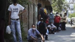 Des Indiens font laqueue pour faire leurs courses, en plein confinement.
