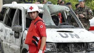 Un miembro de la Cruz Roja frente al vehículo de la ONU atacado en las afueras de Tiro, en el sur del Líbano, el 9 de diciembre de 2011.