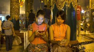 Deux Birmanes consultent leurs smartphones pour aller sur Internet.