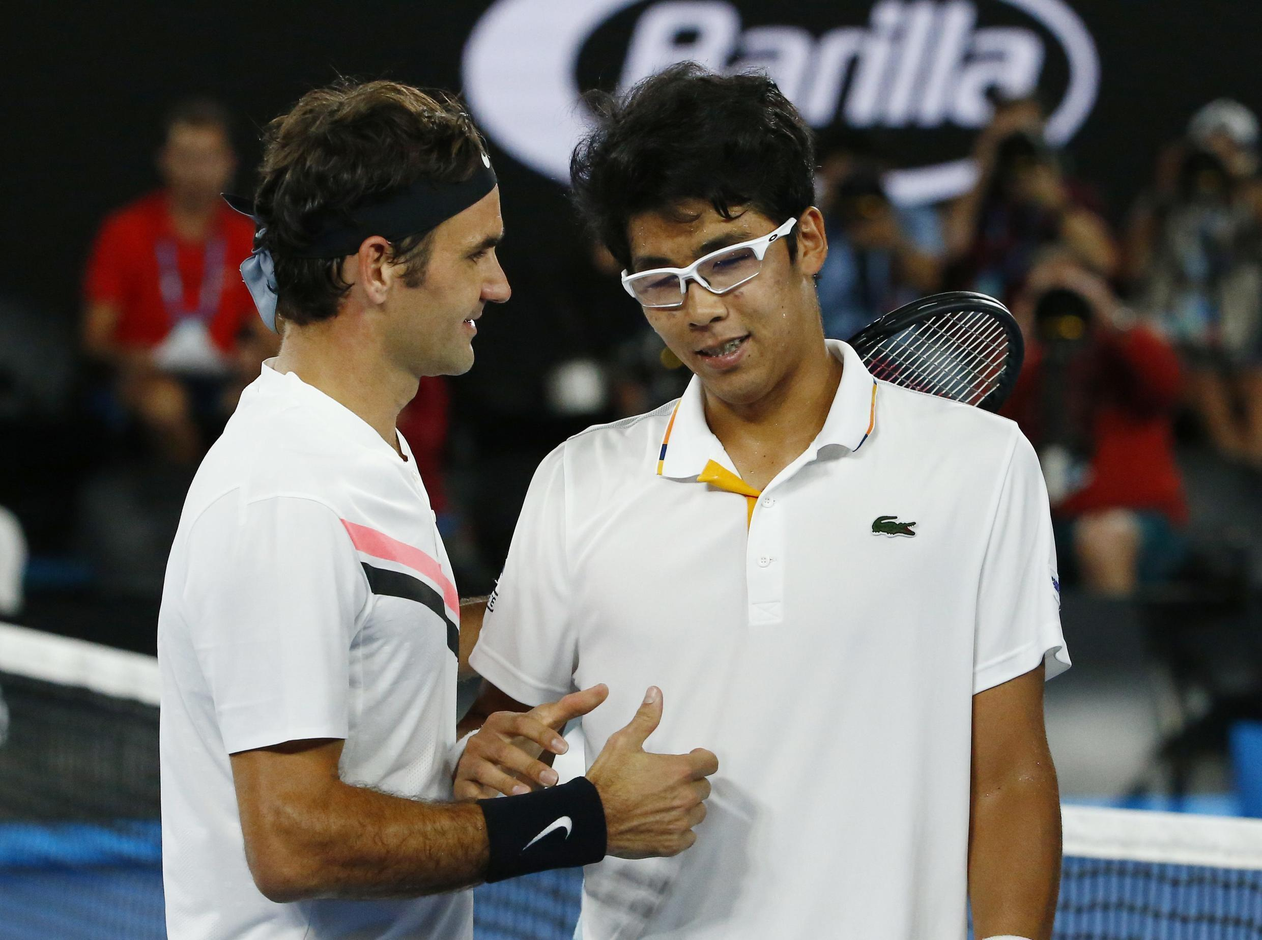 Roger Federer (left) consoles Hyeon Chung after he retired from their Australian Open semi-final.