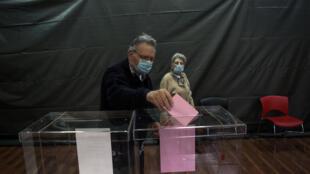 Un hombre con una mascarilla vota en un colegio electoral de Belgrado, Serbia, el 21 de junio de 2020