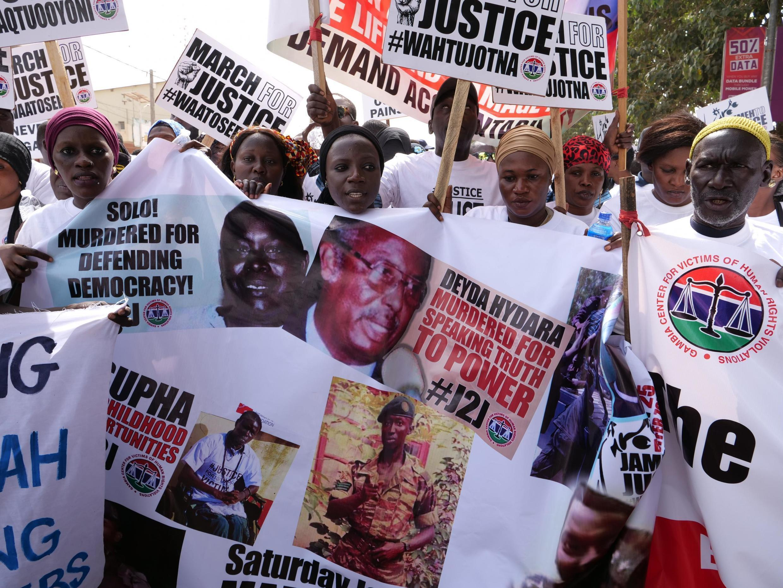 Les manifestants tiennent des banderoles sur lesquelles ont voit le visage des victimes du régime de Yahya Jammeh, l'ancien président de la Gambie, lors d'une manifestation demandant que Yahya Jammeh soit traduit en justice, à Banjul, le 25 janvier 2020.