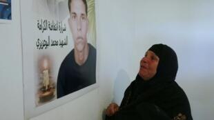 La mère de Mohamed Bouazizi devant un portrait de son fils.