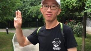 Hu Jia levant les trois doigts de sa main droite ce qui signifie «résistance», «espoir» et «liberté».