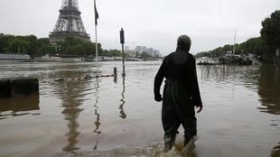 A man walks on a flooded road near his houseboat moored near the Eiffel towel during flooding on the banks of the Seine River in Paris, France, after days of almost non-stop rain caused flooding in the country June 2, 2016.