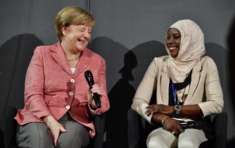 La canciller Angela Merkel con la refugiada Nyima Jadama, de Gambia, durante una reunión con estudiantes refugiados en Berlín, 25 de agosto de 2017.