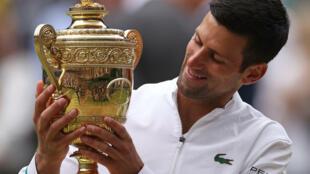 El tenista serbio Novak Djokovic recibe su sexto trofeo de campeón del torneo de Wimbledon, el 11 de julio de 2021 en Londres