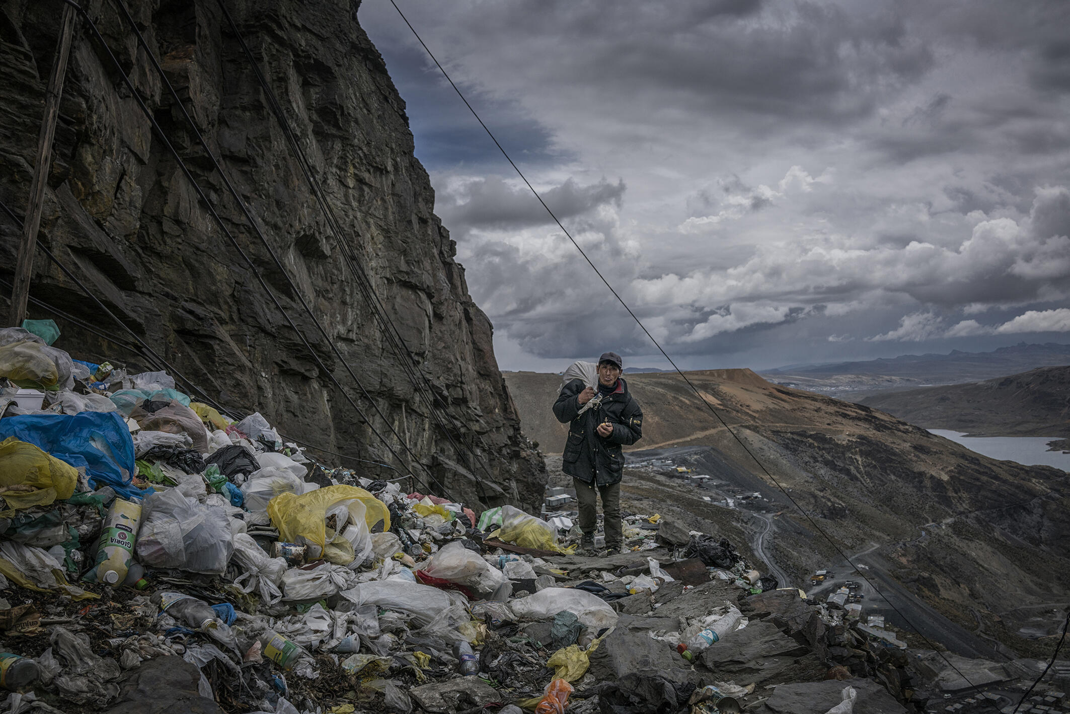 A miner returning home along a precipice littered with single-use plastic trash. La Rinconada, Peru.