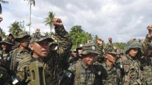 Des rebelles du Front Moro islamique de libération, dans la province de Maguindanao, aux Philippines, célèbrant la signature de l'accord de paix, en 2014.