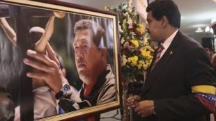 Em foto distribuída pelo palácio de Miraflores, o presidente interino da Venezuela, Nicolás Maduro, observa foto de Hugo Chávez.
