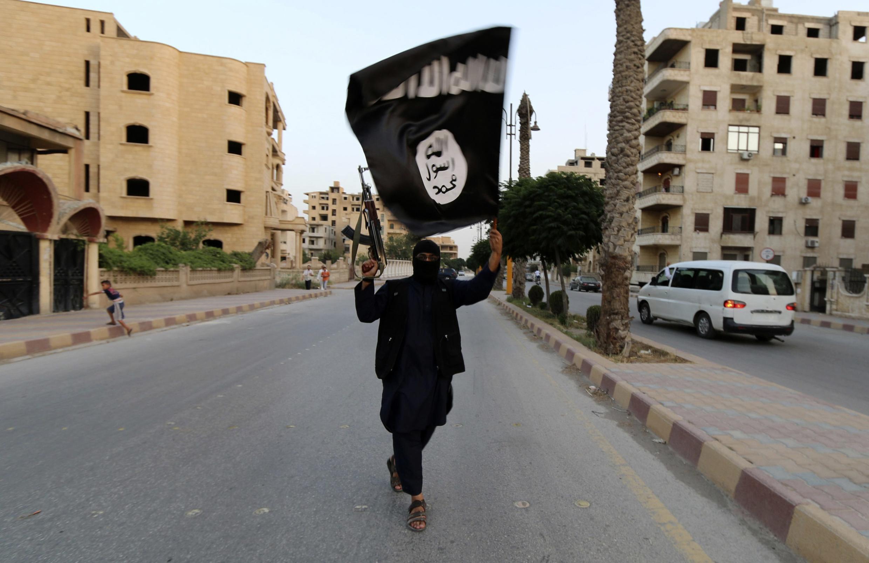 Les jeunes arrêtés voulaient rejoindre la Syrie. Photo : un membre du groupe Etat islamique brandit un drapeau du groupe jihadistes à la Racca en Syrie, le 29 juin 2014.