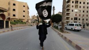 Un membre de l'organisation Etat islamique brandit un drapeau du groupe jihadiste à la Racca (Syrie) après l'annonce de la création d'un «califat islamique», le 29 juin 2014.