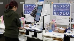 Un client utilise son téléphone portable à la caisse automatique d'un supermarché de Tokyo.