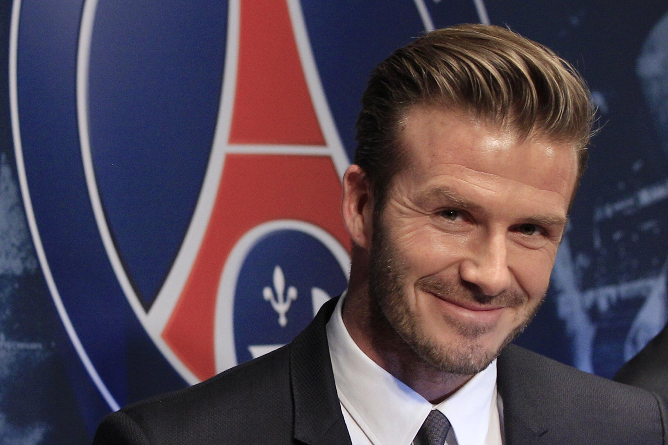 David Beckham, entre o diretor esportivo do PSG, o brasileiro Leonardo (e), e o proprietário do time, Nasser Al-Khelaifi (d).