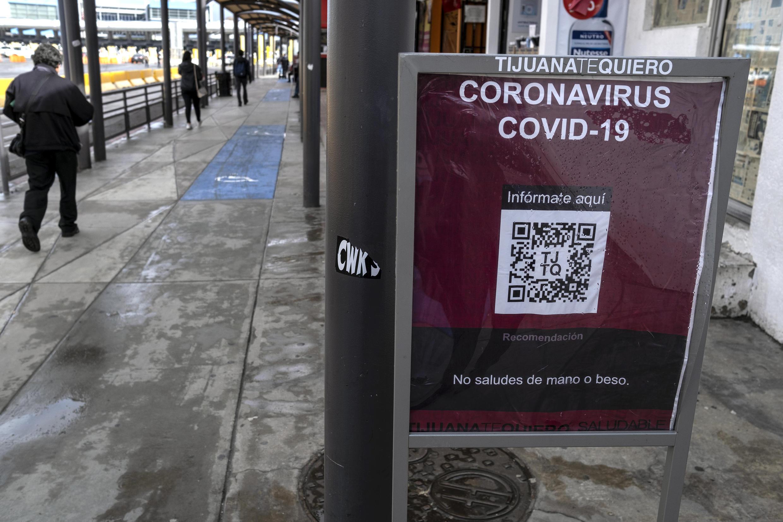 Transeuntes passamao lado de um aviso sobre a Covid-19, na cidade mexicana  de San Ysidro