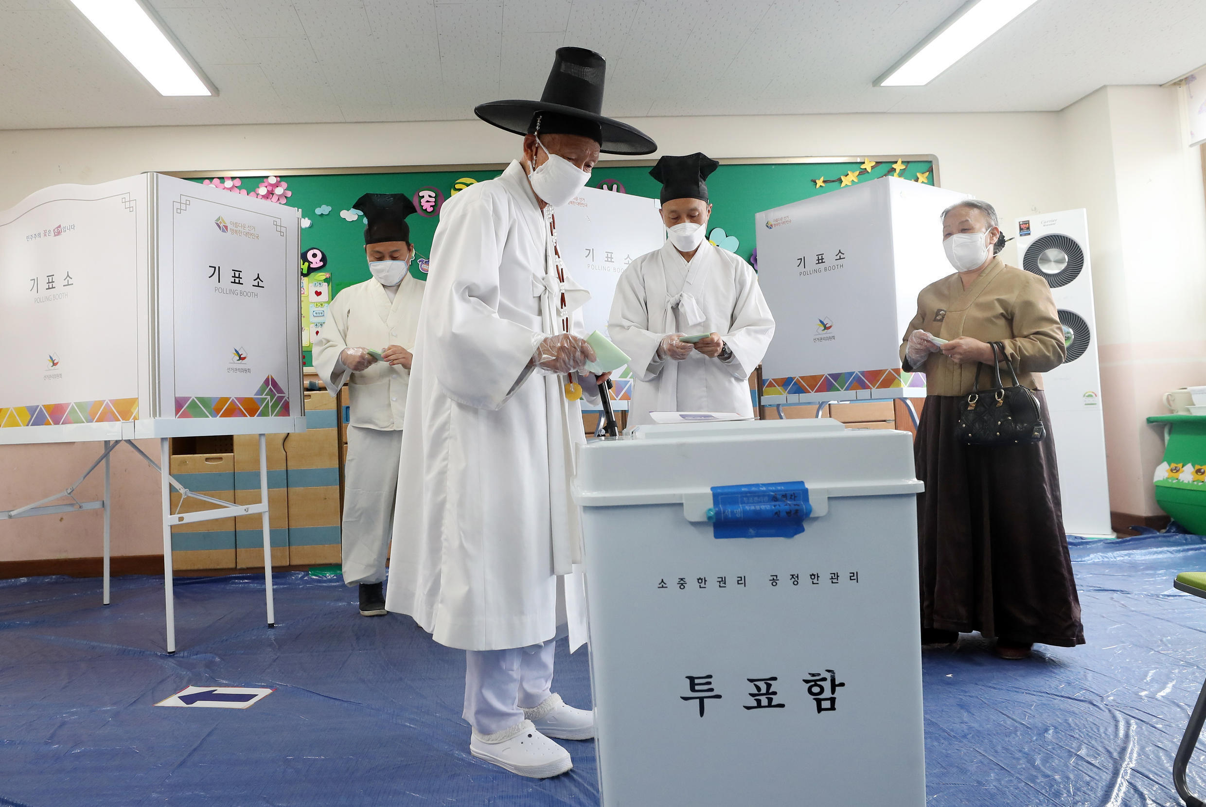 A South Korean in traditional dress casts his ballot