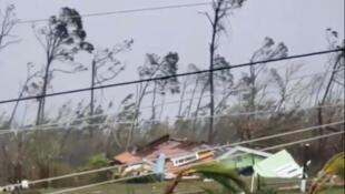 Arbres déracinés, lignes électriques décrochées, débris de maison sur une route alors que l'ouragan traverse Marsh Harbour, dans les Bahamas.