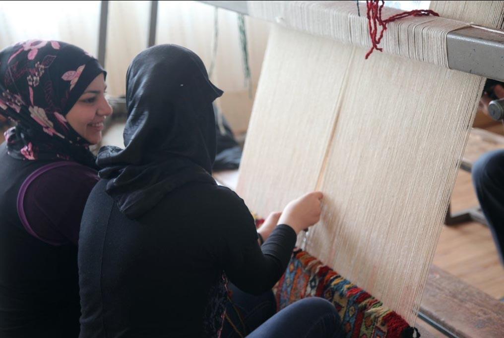 Réfugiées syriennes tissant un tapis dans un atelier turc.