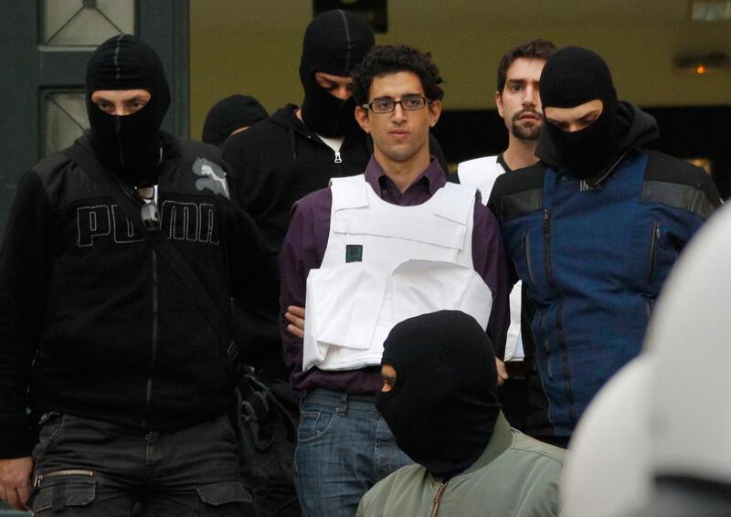 Polícia grega escolta um dos suspeitos detido em Atenas no dia 2 de novembro.