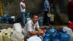 Venezuelanos esperam com latas para pegar água na montanha de Ávila, em Caracas.
