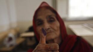 Une femme montre son pouce imprégné d'encre après avoir voté. A Karachi, le 11 mai 2013.