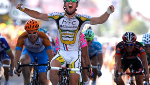 Mark Cavendish celebrates as he crosses the finish line to win the eleventh stage of the Tour de France.