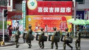 Des patrouilles anti-émeutes dans les rues d'Urumqi, dans la province chinoise du Xinjiang, le 3 juillet 2010 afin d'éviter tout débordement  lors du premier anniversaire des émeutes sanglantes qui ont eu lieu dans la ville.