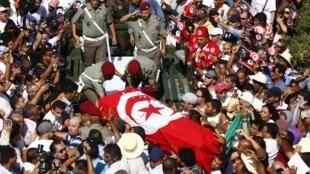 突尼斯情绪激动的民众群集替遇刺身亡的反对派领袖布拉米举行葬礼  2013年7月27日