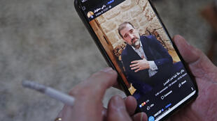 A man watches a Facebook video of Syrian business tycoon Rami Makhlouf who has fallen out with the cash-strapped regime
