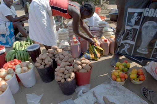 Une commerçante propose divers produits de consomation courante sur une place de marché, en Angola.