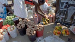 Une commerçante propose divers produits de consommation courante sur une place de marché, en Angola.