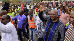 Roch Marc Christian Kabore (d.), ancien président de l'Assemblée nationale burkinabè, salue la foule à son arrivée dans le cortège de l'opposition, le 18 janvier 2014 à Ouagadougou.