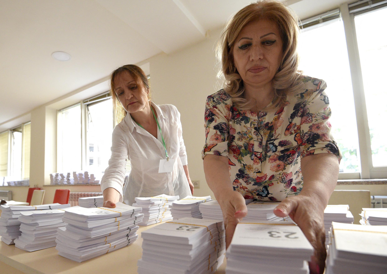 Des membres de la Commission électorale préparent un bureau de vote à Erevan, le 19 juin 2021. Les législatives anticipées, convoquées par le Premier ministre par intérim Nikol Pachinian, affaibli par sa défaite militaire face à l'Azerbaïdjan à l'automne, se tiennent dimanche 20 juin.