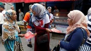 La campagne électorale pour les législatives en Tunisie a pris fin le 4 octobre. 7 millions d'électeurs sont appelés à élire leurs députés. Sur la photo, un membre du parti de Nabil Karoui distribue des prospectus, à Tunis.
