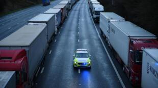 Un vehículo de la policía circula entre la fila de camiones bloqueados en la autopista hacia Dover, en Inglaterra, el 22 de diciembre de 2020