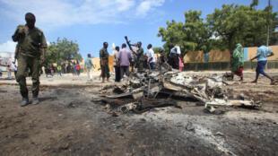 Un policier somalien, près de la carcasse d'une voiture détruite par une explosion attribuée aux islamistes shebabs, devant le département des enquêtes criminelles à Mogadiscio, le 31 juillet 2016.