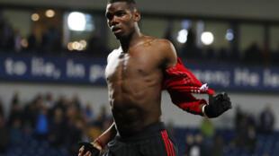 Kiungo wa Manchester united, Paul Pogba, akivua jezi yake kuigawa kwa mashabiki wa timu hiyo.