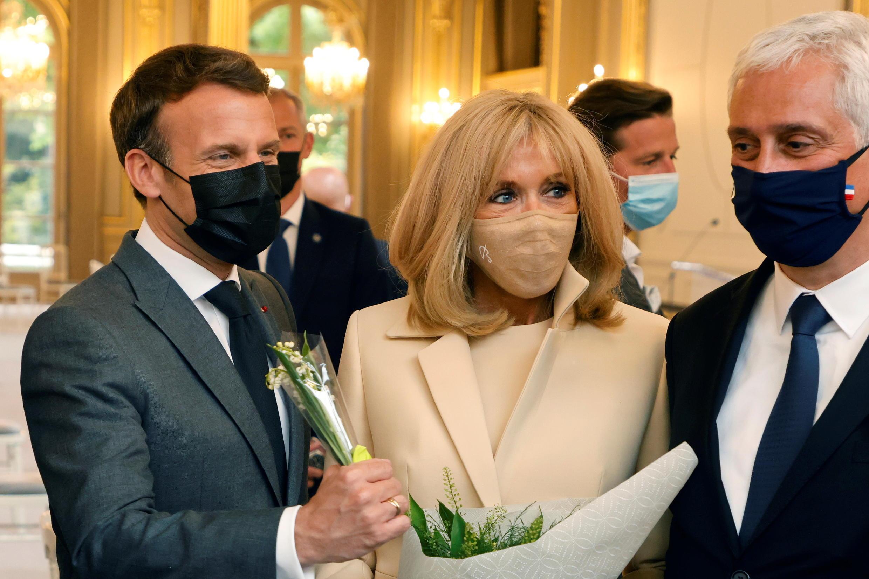 O presidente francês Emmanuel Macron, sua esposa Brigitte e o CEO da Rungis Market, Stephane Layani, participam da tradicional cerimônia do Lírio do Vale no Palácio do Eliseu em Paris, França, em 1º de maio de 2021. Ludovic Marin / Pool via REUTERS