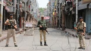 Indian security personnel stand guard along a deserted street during restrictions in Jammu, August 5, 2019.