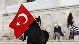 Une femme tient le drapeau turque devant la mosquée Fatih à Istanbul,  le 11 décembre 2016.