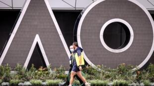 Dos hombres pasan frente a las letras del logotipo del Abierto de Australia de tenies, el 30 de enero de 2021 en Melbourne