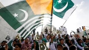 Pakistani and Kashmiri flags are waved in an expression of solidarity with Kashmir during a ceremony to marking Pakistan's 72nd Independence Day at the Mausoleum of founder Muhammad Ali Jinnah in Karachi, 14 August 2019.