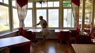 Une responsable d'hôtel prépare des tables pour sa réouverture, à Altaussee le 22 avril 2020.