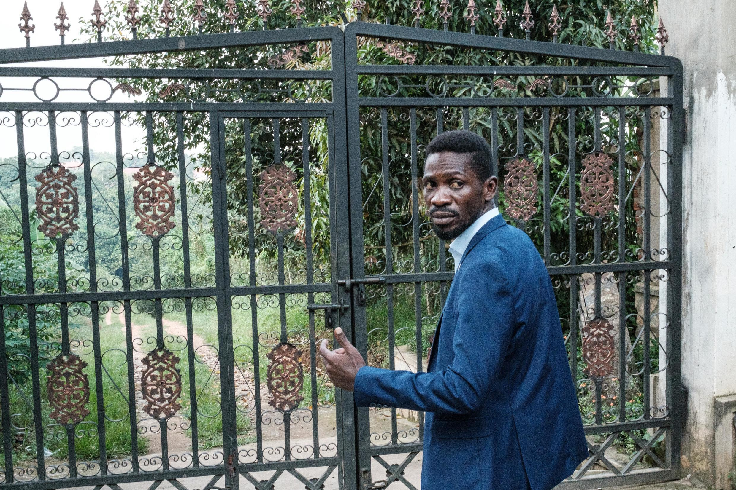 Ugandan opposition leader Bobi Wine at the gate of his home, which soldiers have surrounded after he alleged mass electoral fraud