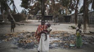 Mama huyu na mtoto wake wamesimama mbele ya kijiji kimoja, karibu na mji wa Macomia (Cabo Delgado) baada ya shambulio, Agosti 24, 2019.
