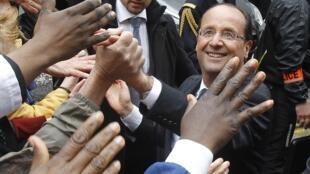 O novo presidente da França, o socialista François Hollande, cumprimenta  parisienses durante visita à prefeitura da capital, nesta terça-feira.