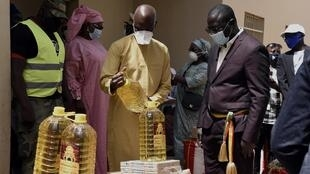 Mansour Faye (boubou jaune), le ministre du Développement communautaire et de l'Equité sociale, distribue l'aide alimentaire à Yenn, le 28 avril 2008.