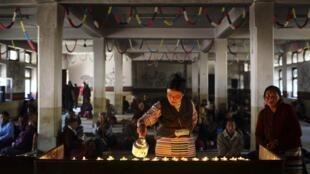 Một phụ nữ Tây Tạng tại Kathmandu đốt đèn nến trong buổi lễ tưởng niệm các nạn nhân bạo động và những người Tây Tạng tự thiêu chống Trung Quốc, ngày 17/11/2012.